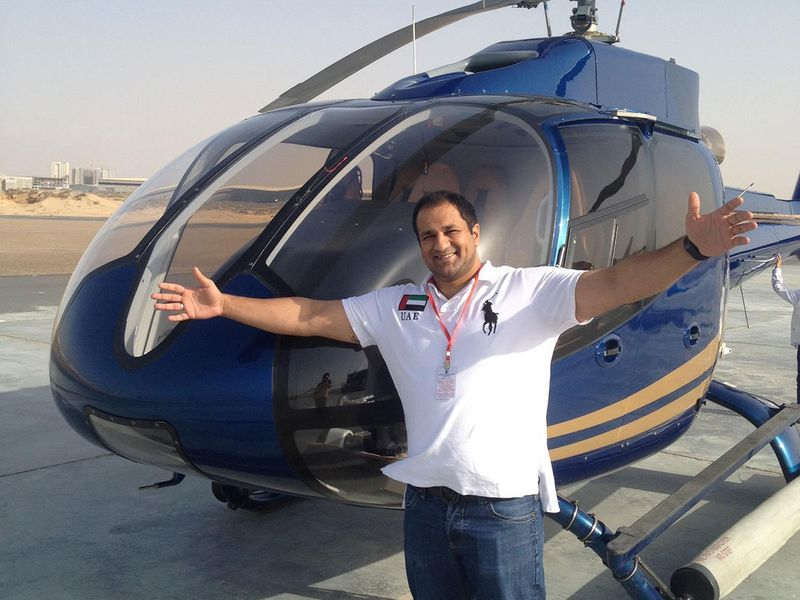 Com Mirza beside a helicopter