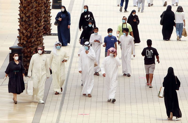 Kuwaitis wearing face masks walk inside