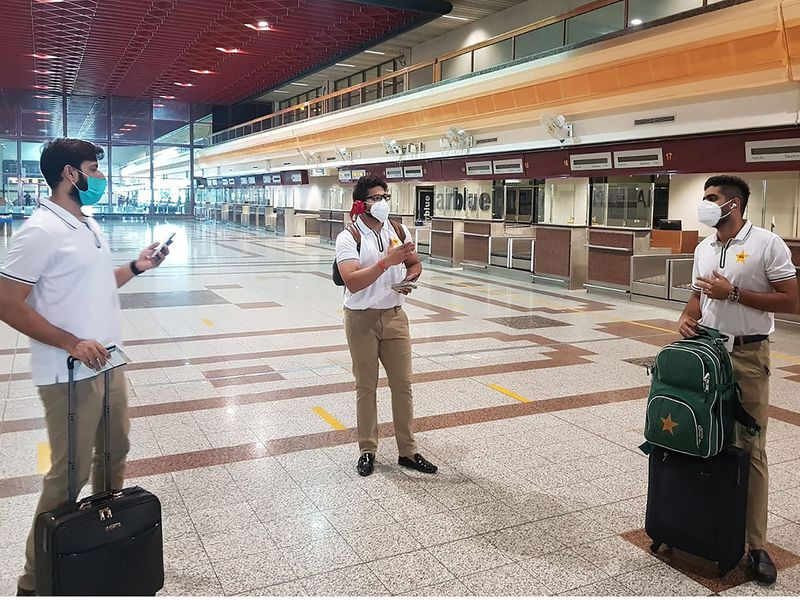 Pakistani cricketers Babar Azam (R), Imad Wasim (L) and Imam-ul-Haq (C) wearing facemasks arrive at the Allama Iqbal International airport before their departure to England