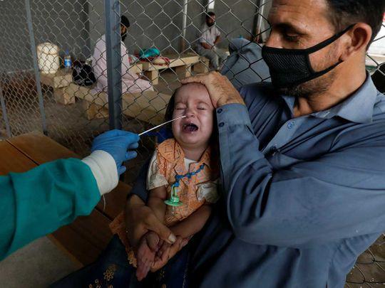 A paramedic wearing protective gloves takes a nasal swab karachi Pakistan