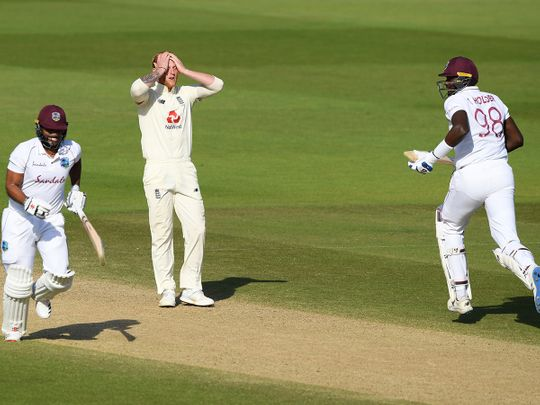 England captain Ben Stokes reacts as West Indies captain Jason Holder, right, and John Campbell, left, take a run