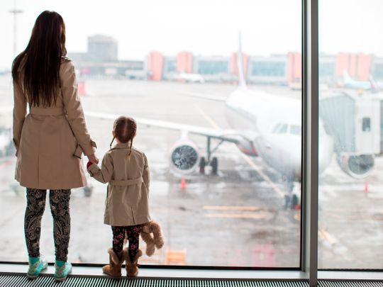 Child and mother watching plane in airport