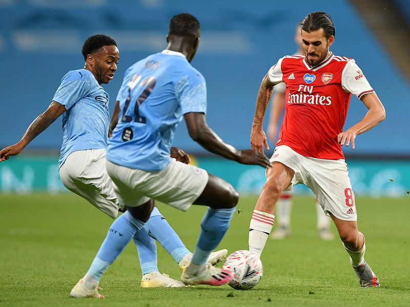 Arsenal's Dani Ceballos right, battles for the ball with Manchester City's Raheem Sterling, left, and Benjamin Mendy during the FA Cup semifinal soccer match between Arsenal and Manchester City at Wembley in London, England, Saturday, July 18, 2020. (AP Photo
