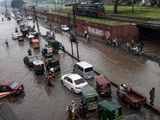 Commuters flood street monsoon rain Lahore Pakistan