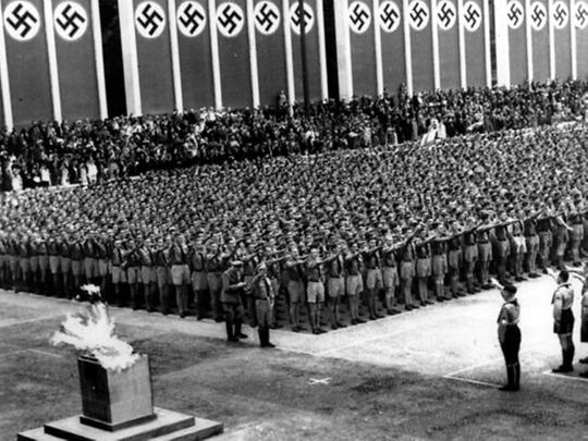 German Nazi soldiers line up in front of the Olympic torch during the opening ceremonies of the XI Summer Olympic Games at the Lustgarten in Berlin, Germany.