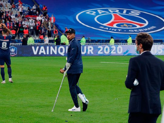 Paris St-Germain's Kylian Mbappe walks with crutches after the French Cup final win over St-Etienne