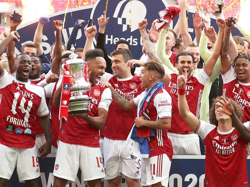 Arsenal's Pierre-Emerick Aubameyang holds the trophy celebrating with team mates