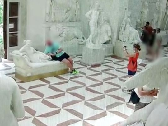 A tourist damaged a 19th-century sculpture after he sat on it to pose for a picture.
