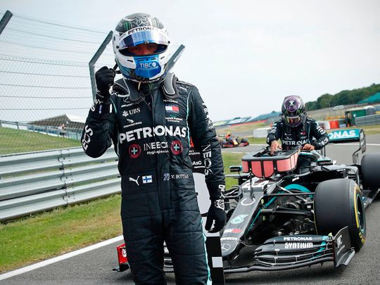 Mercedes' Finnish driver Valtteri Bottas celebrates in the pit lane as Mercedes' British driver Lewis Hamilton (back) gets out of his car after the qualifying session of the F1 70th Anniversary Grand Prix at Silverstone on August 8, 2020 in Northampton. - This weekend's race will commemorate the 70th anniversary of the inaugural world championship race, held at Silverstone in 1950. (Photo by ANDREW BOYERS / POOL / AFP)