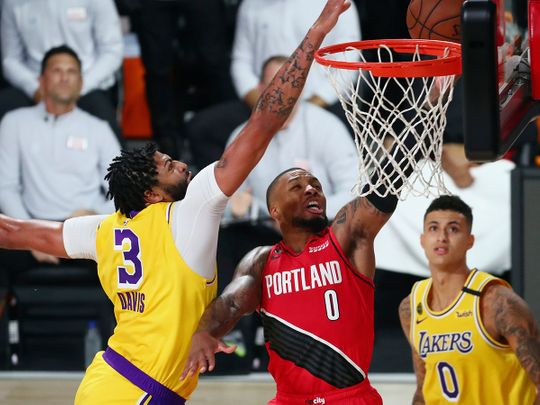 Los Angeles Lakers forward Anthony Davis blocks a shot by Portland Trail Blazers guard Damian Lillard