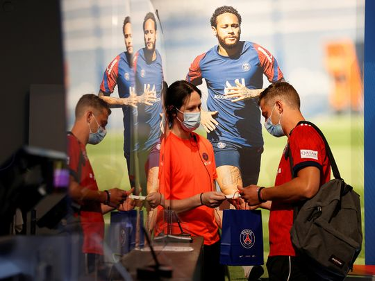 A fan buys a club shirt in the PSG store in Paris ahead of the Champions League final against Bayern Munich