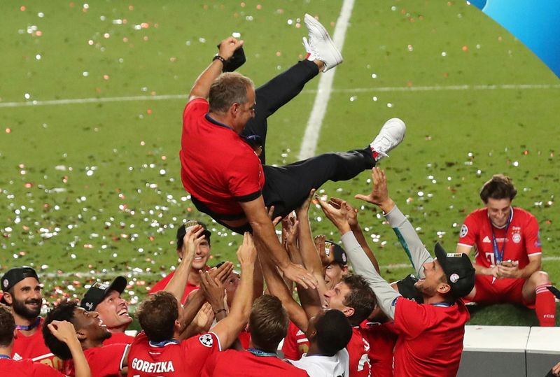 Bayern Munich players celebrate winning the Champions League as they throw coach Hansi Flick above them.