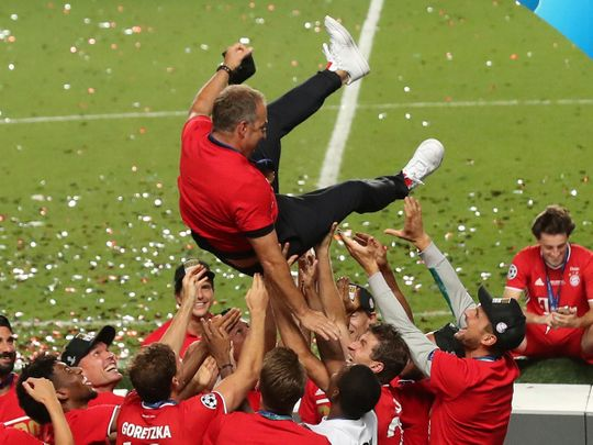 Bayern Munich players celebrate winning the Champions League as they throw coach Hansi Flick in the air