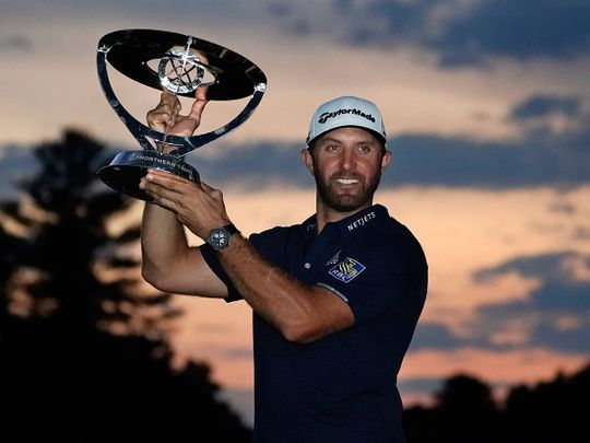 Dustin Johnson holds the trophy after winning the Northern Trust tournament at TPC Boston