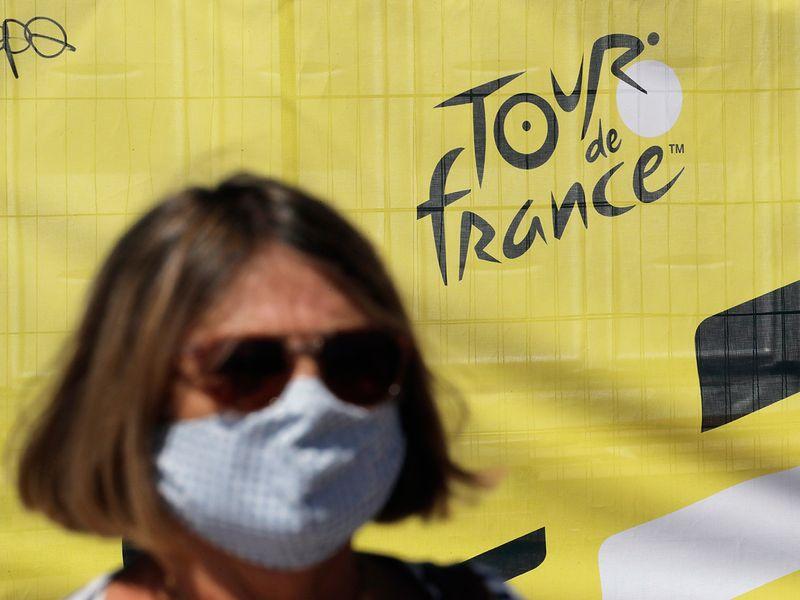 A woman wears a face mask as she walks past a Tour de France logo in Nice