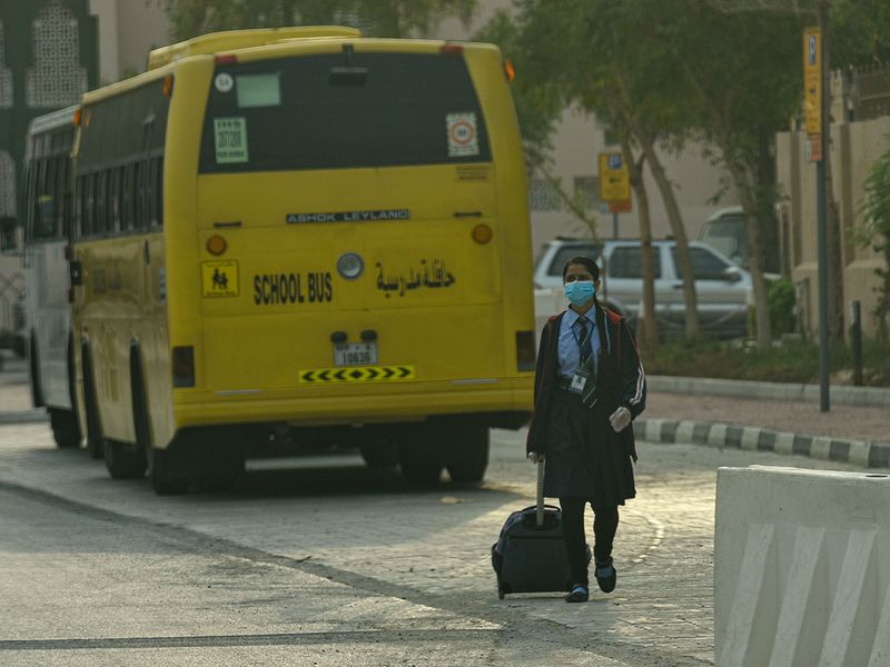 A student arrives at the Indian High School in Dubai on first day of school after summer vacations.