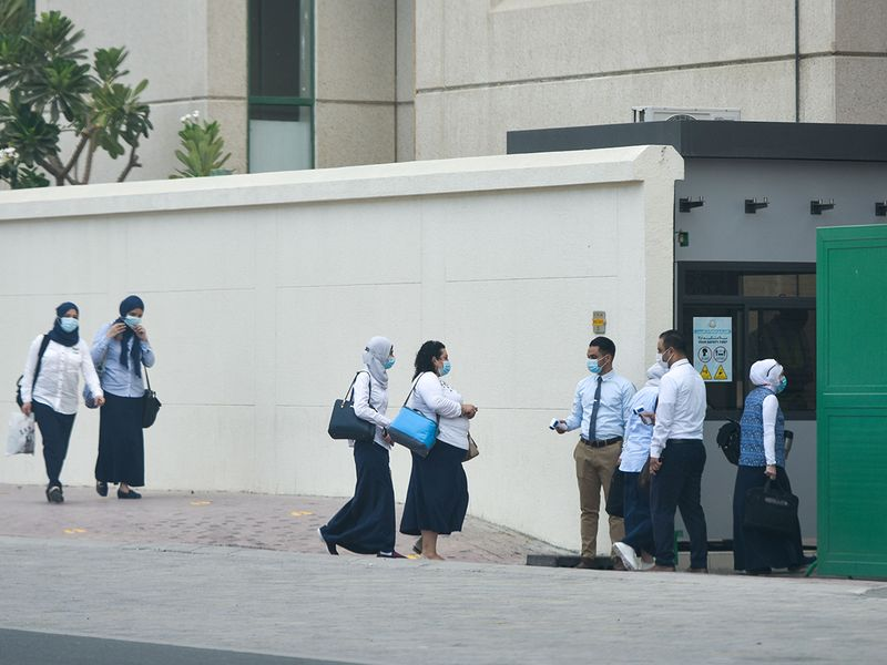 Teachers and staff members go through a temperature check before entering the premises of Al Rashid Al Saleh Private School in Dubai.