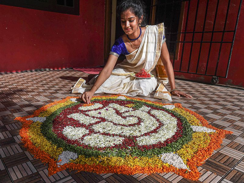 A young woman prepares 'Pookalam' on the occasion of Onamfestival, amid the ongoing coronavirus pandemic, in Chennai.