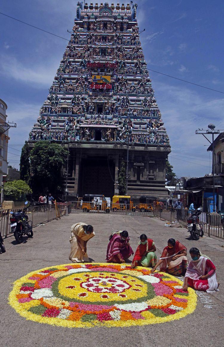 Woman making  pookalam (flower rangoli) on the occasion of Onam festival at Kapaleeshwarar Temple in Chennai.