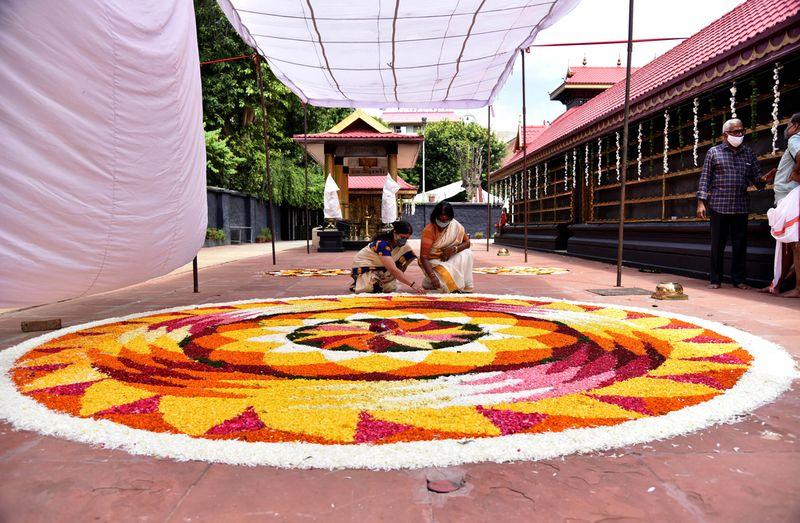 Women decorate a rangoli made by using flowers of several colours to welcome Bhagwan Mahabali to mark the Onam festival, at Uttara Guruvayurappan Temple Mayur Vihar, in New Delhi.