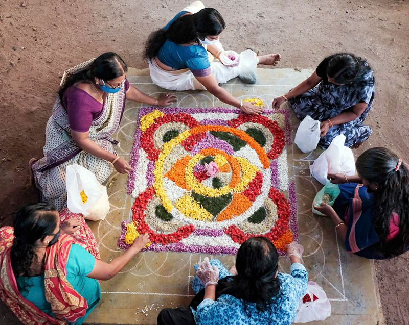 Women giving finishing touches to a pookalam or flower carpet for Onam festival in Kochi.