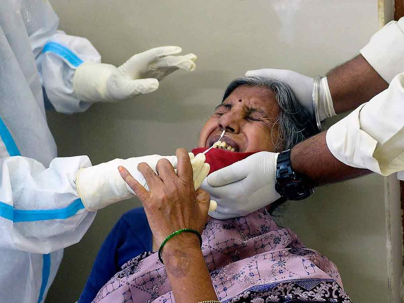 A health worker (L) wearing a Personal Protective Equipment (PPE) suit collects a swab sample from a woman to test for the Covid-19 coronavirus at a primary health centre in Hyderabad on September 3, 2020
