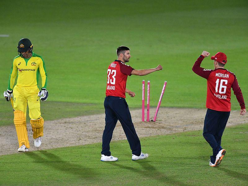 England's Mark Wood, center, celebrates with captain Eoin Morgan