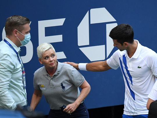 Novak Djokovic comes to the line judge's aid after hitting her with a ball at the US Open