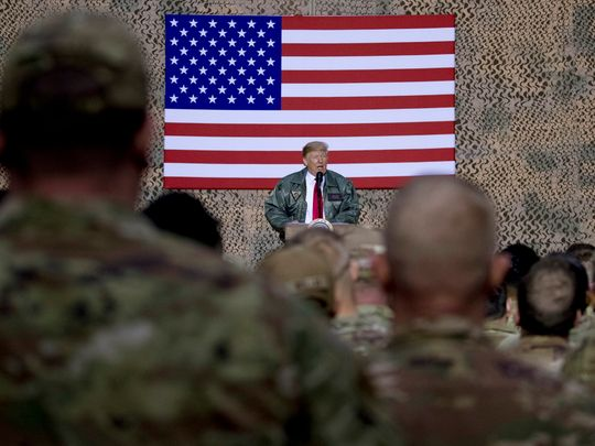 In this December 2018, file photo, President Donald Trump speaks to members of the military at a hangar rally at Al Asad Air Base, Iraq. Among veterans and military families across the United States, there are sharply mixed feelings about the new reports that Trump made multiple disparaging comments about the US military.