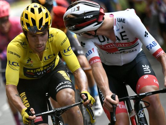 Jumbo rider Slovenia's Primoz Roglic wearing the overall leader's yellow jersey (L) and Team UAE Emirates rider Slovenia's Tadej Pogacar ride during the 13th stage of the 107th edition of the Tour de France cycling race, 191 km between Chatel-Guyon and Puy Mary, on September 11, 2020. (Photo by Marco Bertorello / AFP)