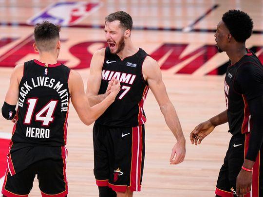 Miami Heat's Tyler Herro, left, Goran Dragic and Bam Adebayo celebrate the Game 4 win over Boston Celtics.