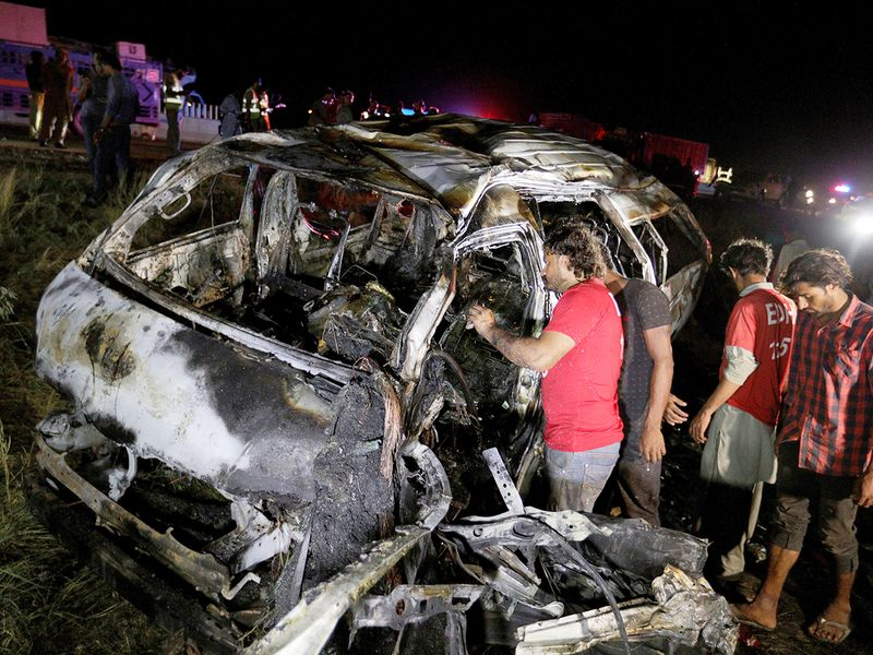 Rescue workers examine a burnt van at the accident site on a highway about 50 kilometers (31 miles) outside of Karachi, Pakistan, Saturday, Sept. 26, 2020.
