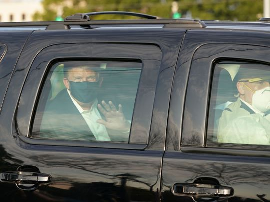 Trump waves from the back of a car in a motorcade outside of Walter Reed Medical Center in Bethesda, Maryland on October 4, 2020