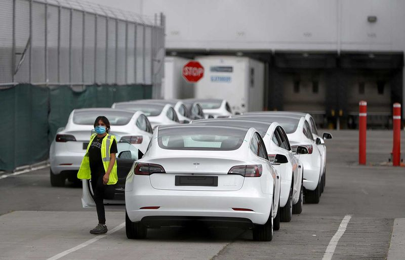 A worker exits a Tesla Model 3 electric vehicle at Tesla's primary vehicle factory n Fremont, California, U.S. May 11, 2020. REUTERS/Stephen Lam/File Photo