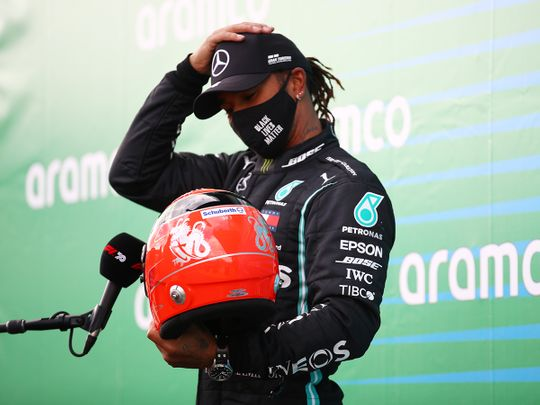 Mercedes' Lewis Hamilton receives one of Michael Schumacher's helmets from the German's son, Mick, after winning the Eifel Grand Prix.