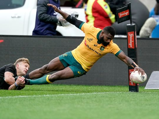 Australia's Marika Koroibete, right, scores a try in the tackle of New Zealand's Damian McKenzie during the Bledisloe Cup.