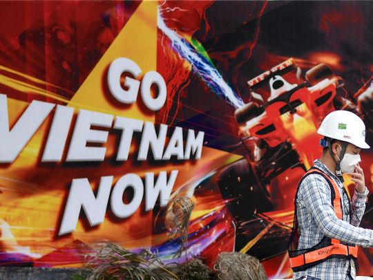 A worker walks past hoarding at the Formula One Vietnam Grand Prix race track site in Hanoi.