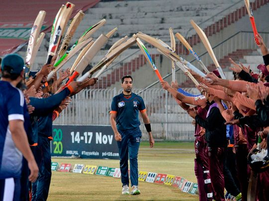 Teammates and opponents give a guard of honour to Pakistani cricketer Umar Gul during the National T20 Cup in Rawalpindi.