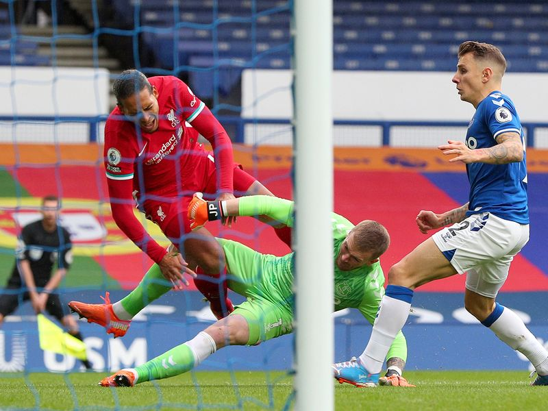 Virgil van Dijk is clobbered by Everton's Jordan Pickford