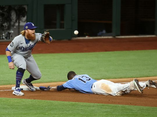 Tampa Bay Rays left fielder Manuel Margot (13) reaches third base ahead of the tag by Los Angeles Dodgers third baseman Justin Turner