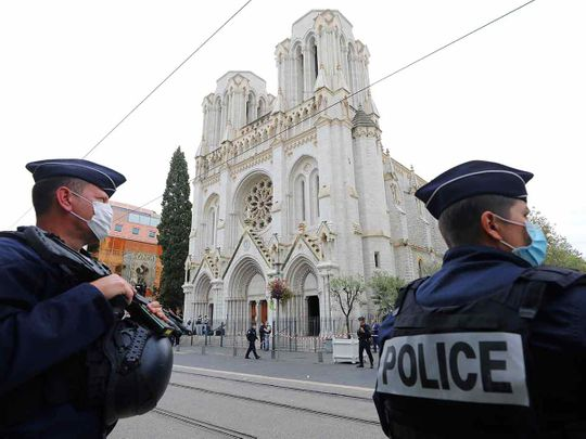 French policemen stand guard the site of a knife attack at the Basilica of Notre-Dame de Nice in Nice on October 29, 2020, as forensics officers prepare to enter.