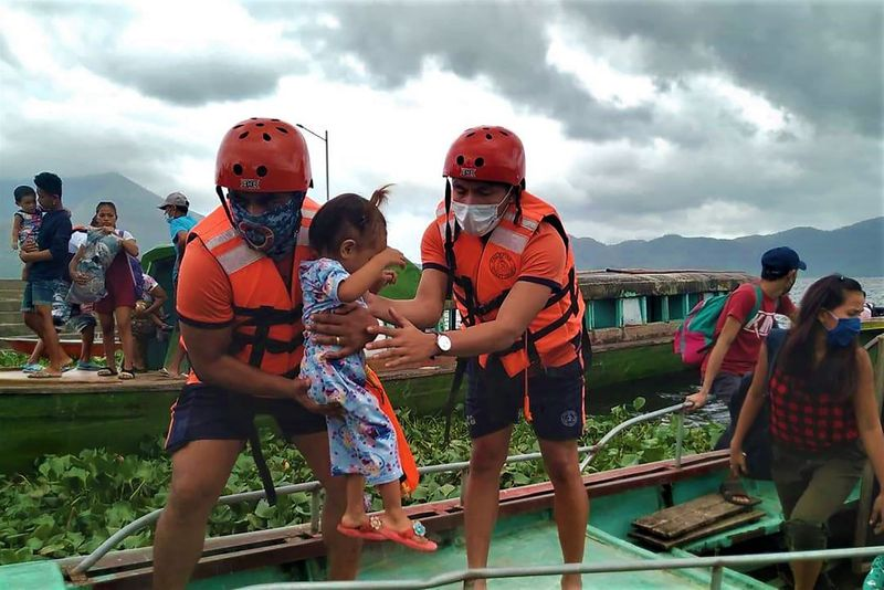 Philippine Coast Guard personnel evacuate residents from the coastal villages of Buhi town ahead of Typhoon Goni's landfall.