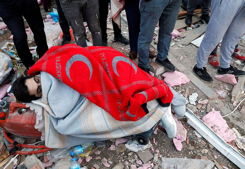 An earthquake survivor is covered with blankets