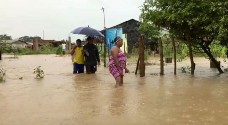 People wade in floodwaters caused by Hurricane Iota in Cartagena, Colombia.