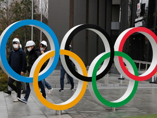 Pedestrians wear masks outside the National Stadium Olympic Rings in Tokyo