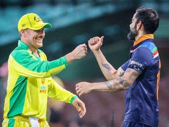 Australia's David Warner and India's Virat Kohli share a joke during the first ODI