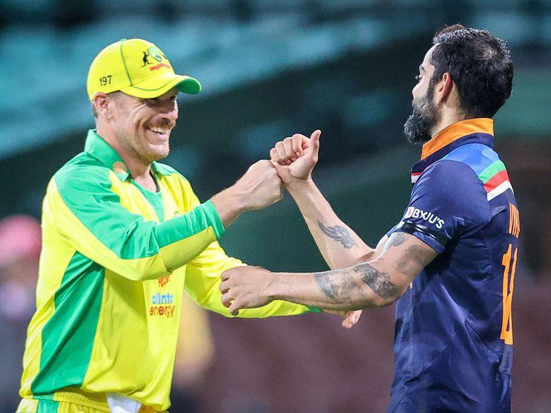 Australia's captain Aaron Finch (L) bumps fists with India's captain Virat Kohli