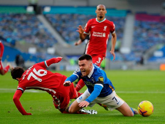 Liverpool's Neco Williams fouls Brighton's Irish striker Aaron Connolly for a penalty