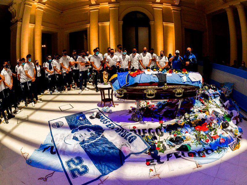 Members of Argentine football team Gimnasia y Esgrima La Plata pay tribute to the coffin of Diego Maradona