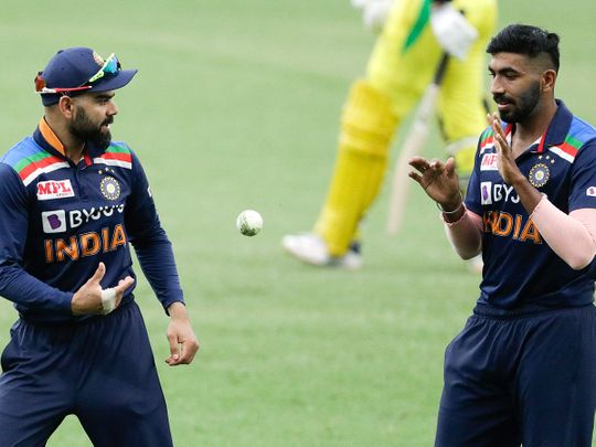 Virat Kohli passes the ball to teammate Jasprit Bumrah